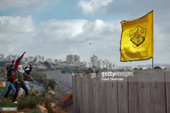 NI'ILIN WEST BANK JANUARY 01 Palestinians hurl stones at Israeli troops on the other side of Israel's controversial separation barrier during a Fatah...