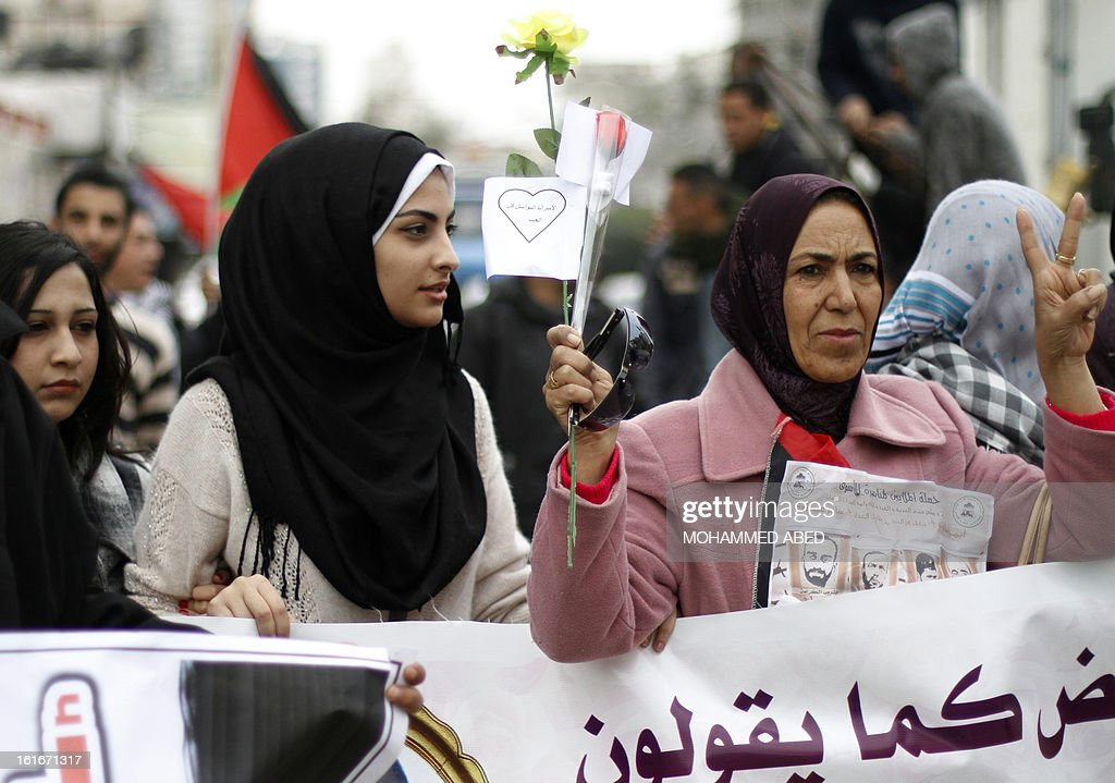 Palestinians in solidarity with hunger strike prisoner Samer Issawi, who is held in an Israeli jail, flash the sign for victory whilst holding flowers and banners during a protest on Valentine's Day in Gaza City on February 14, 2013. A United Nations official on February 13, expressed concern about the wellbeing of Palestinian detainees in Israeli prisons and in particular about the condition of Issawi.