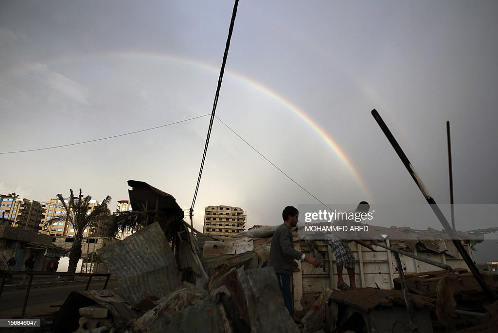 Palestinians inpect the rubble of a destroyed house as a rainbow arcs over Gaza City on November 23, 2012. Israeli politicians returned to the campaign trail as the streets of Gaza came back to life after a truce ended eight days of bloodshed, with both sides claiming victory while remaining wary. AFP PHOTO/MOHAMMED ABED