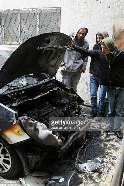 Palestinians inspect a burnt car in the West Bank village of Nabi Elias near Qalqilya after it was set abalze by unknown attackers in what appeared...