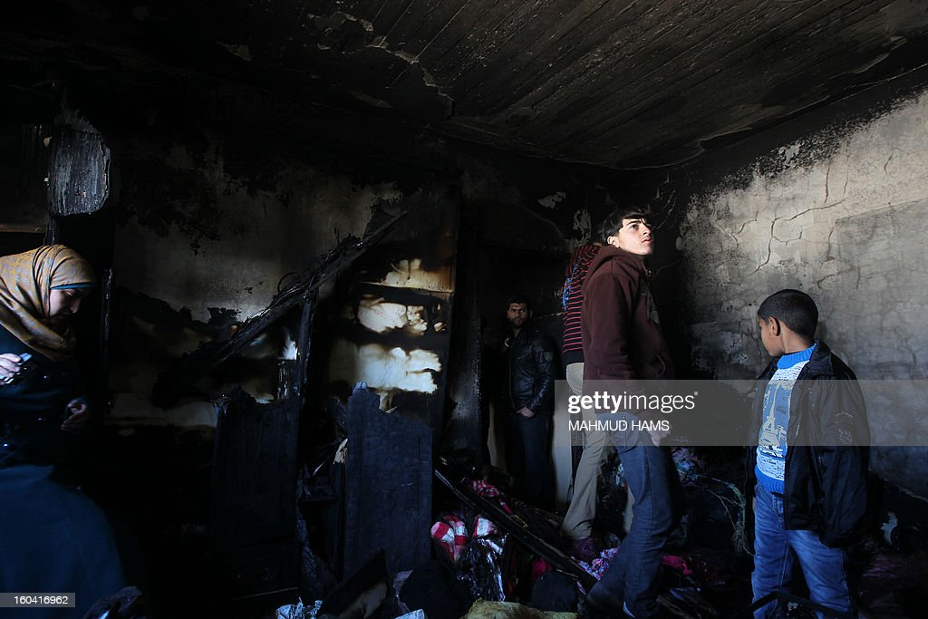 Palestinians inspect a burnt room after a fire swept over a house in Gaza City on January 31, 2013. Hazem Dheir, his wife Sahar and their four young children were killed in the fire that is believed to have started by an electrical fault.