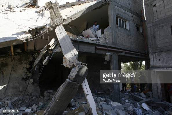 Palestinians inspect a house which police said was destroyed in an Israeli air strike in Khan Younis in southern Gaza Strip Israel officially...