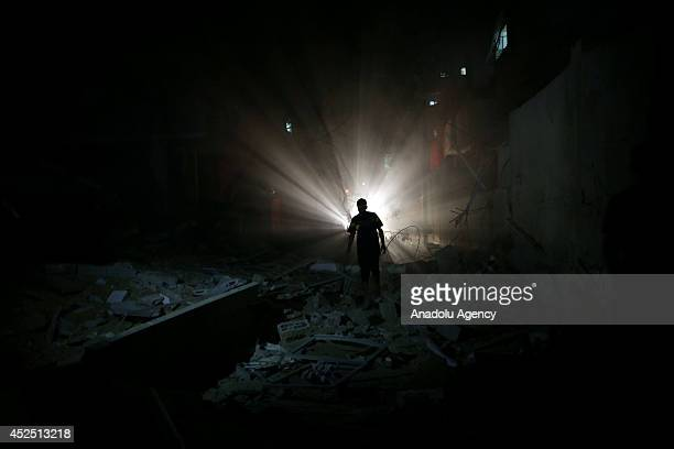 Palestinians inspect destroyed buildings and collect usable stuff following an Israeli air assault staged within the scope of Operation Protective...