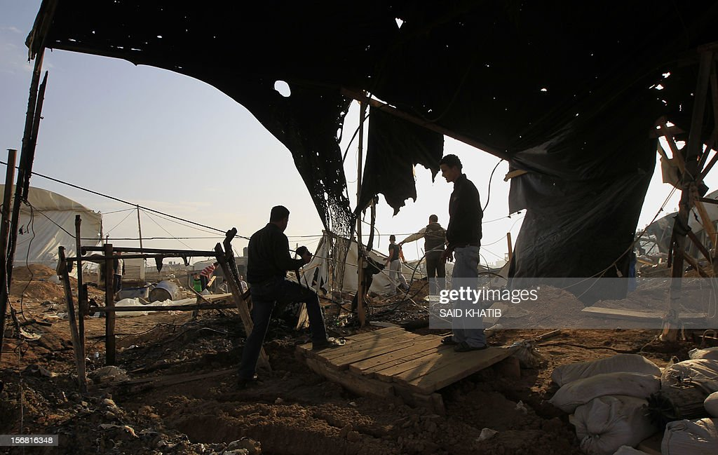 Palestinians inspect destroyed tents near bombed smuggling tunnels between the southern Gaza Strip and Egypt in the border town of Rafah on November 22, 2012. A ceasefire took hold in and around Gaza after a week of cross-border violence between Israel and Palestinian militants that killed at least 160 people.