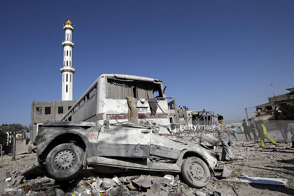 Palestinians inspect the damaged cars following an Israeli airstrike on the village of Beit Lahia in the northern Gaza Strip on November 18, 2012. A ground invasion of the Gaza Strip would lose Israel much international sympathy and support, British Foreign Secretary William Hague warned.