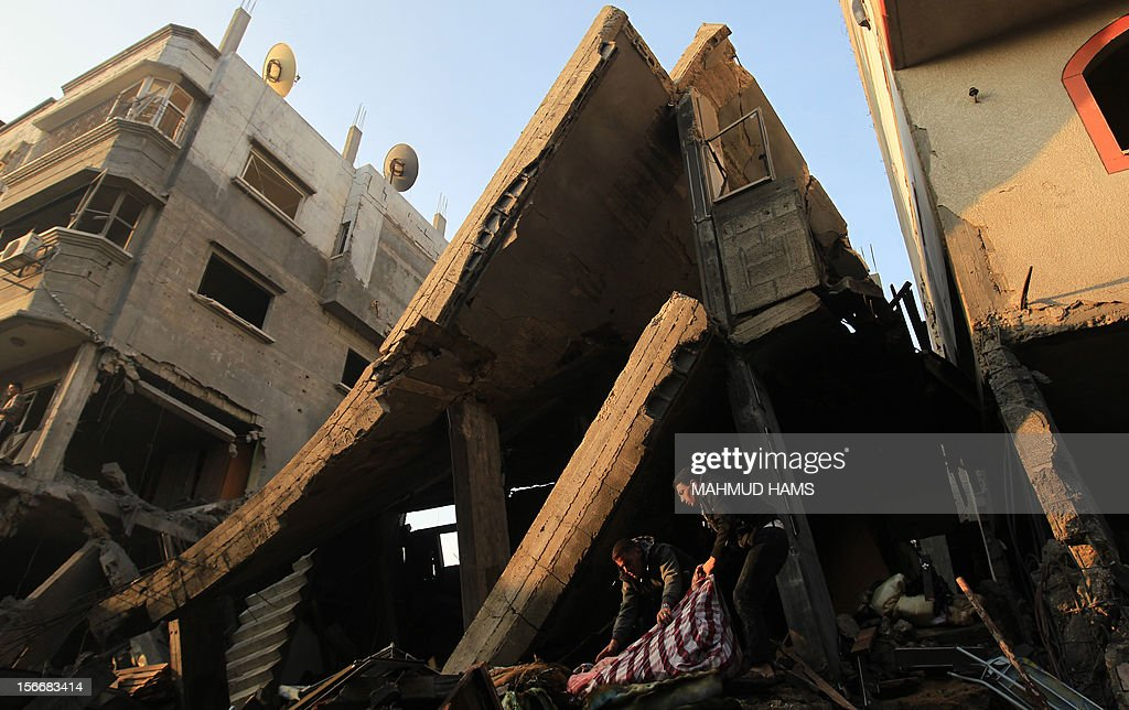 Palestinians inspect the debris of a destroyed home following an Israeli air strike in Gaza City, on November 19, 2012. Israeli air strikes on Sunday killed 31 Palestinians in the bloodiest day so far of its air campaign on the Gaza Strip, as diplomatic efforts to broker a truce intensified.