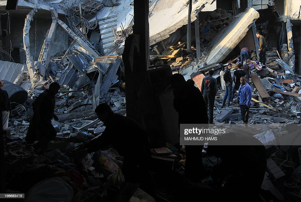Palestinians inspect the debris of a destroyed home following an Israeli air strike in Gaza City, on November 19, 2012. Israeli air strikes on Sunday killed 31 Palestinians in the bloodiest day so far of its air campaign on the Gaza Strip, as diplomatic efforts to broker a truce intensified. AFP PHOTO/MAHMUD HAMS