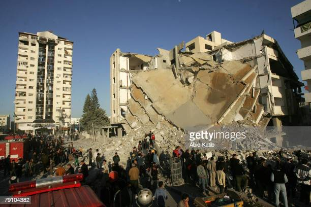 Palestinians inspect the destroyed Hamas Interior Ministry building after it was destroyed in an Israeli air strike January 18 2008 in Gaza City the...