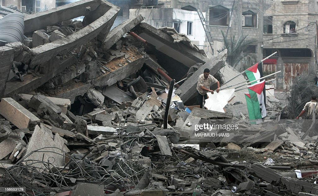 Palestinians inspect the destroyed office building of Hamas Prime Minister Ismail Haniya in Gaza City on November 17, 2012. Israeli air strikes hit the cabinet headquarters of Gaza's Hamas government, the group said early on November 17, with eyewitnesses reporting extensive damage to the building. AFP PHOTO / MAHMUD HAMS