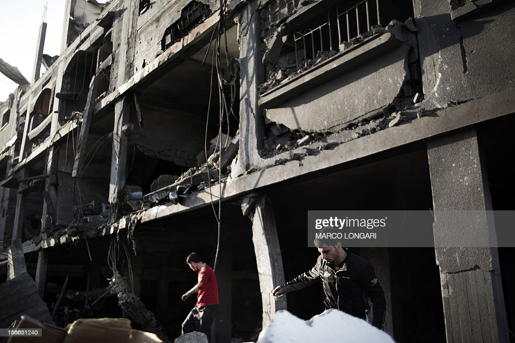 Palestinians inspect their damaged house following Israeli air strikes on the village of Beit Lahia in the northern Gaza Strip on November 18, 2012. Israeli war planes hit a Gaza City media centre and homes in northern Gaza in the early morning, as the death toll mounted, despite suggestions from Egypt's President Mohamed Morsi that there could be a 'ceasefire soon.'AFP PHOTO/MARCO LONGARI