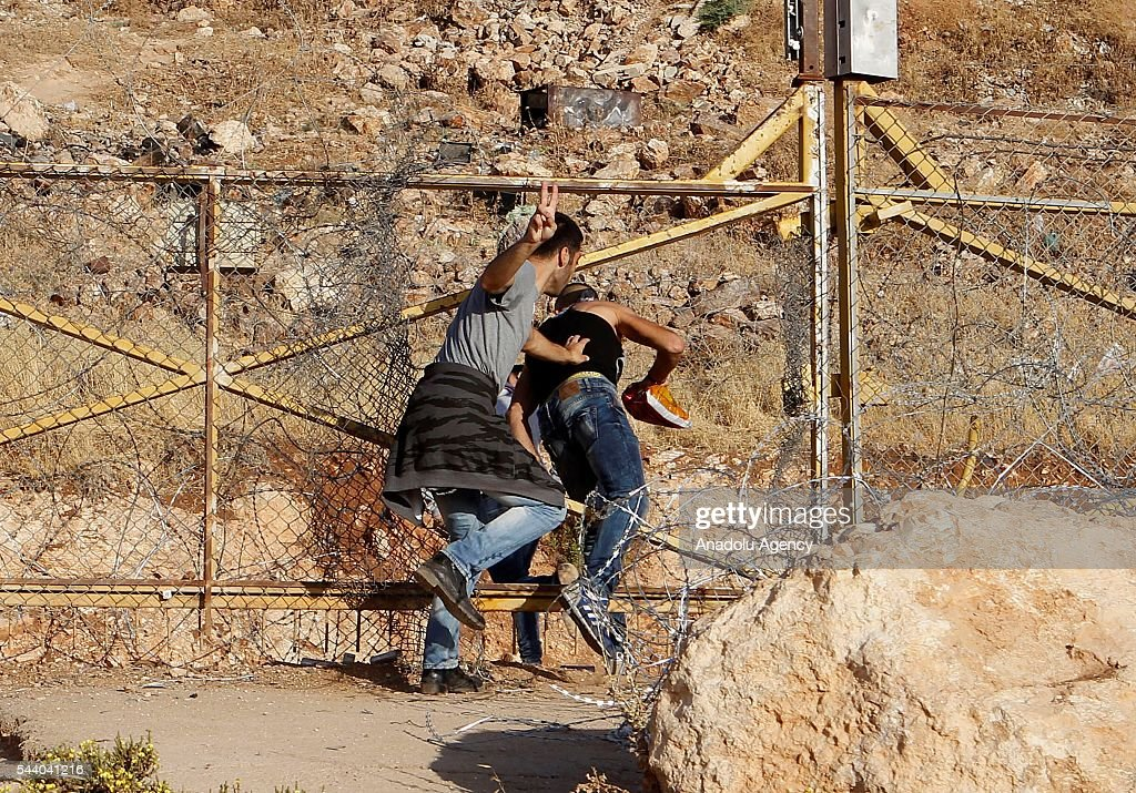 Palestinians jump on fences as they try to pass Jerusalem to attend the friday prayer at Al-Aqsa Mosque during the Islamic holy fasting month of Ramadan, in Bethlehem, West Bank on July 1, 2016. Israeli Authorities had been put entrance restriction that allows Palestinian women, children under 12 and men older than 45 to enter the compound.