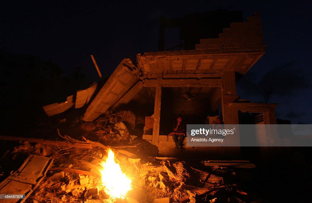 Palestinians light a fire at night among the debris of destroyed buildings as Palestinians start to return their homes during ceasefire in al-Shaaf neighborhood Gaza City, Gaza on August 31, 2014.