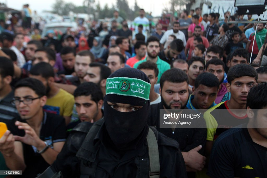 Palestinians listen the press statement of the Ezzeddin al-Qassam Brigades, the armed wing of Palestinian resistance faction Hamas, in the Shujaya neighborhood in eastern Gaza City on August 27, 2014.