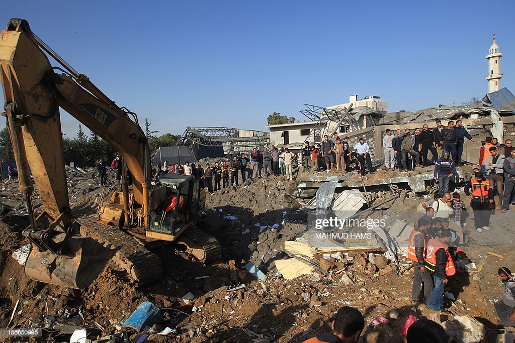 Palestinians look at the aftermath of a destroyed house following an Israeli air strike on Gaza City on November 18, 2012. Fresh Israeli air strikes hit a Gaza City media centre and homes in northern Gaza in the early morning, as the death toll mounted, despite suggestions from Egypt's President Mohamed Morsi that there could be a 'ceasefire soon.'