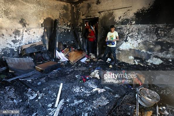 Palestinians look at the damage after a house was set on fire by Jewish settlers in the West Bank village of Duma on July 31 2015 A Palestinian...
