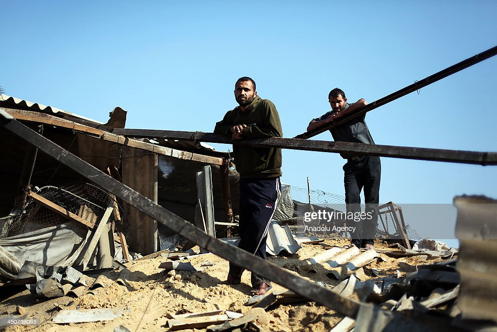 Palestinians look at the damage in a chicken farm after it was hit by an Israeli air strike in Khan Yunis in the southern Gaza Strip on November 20, 2013.