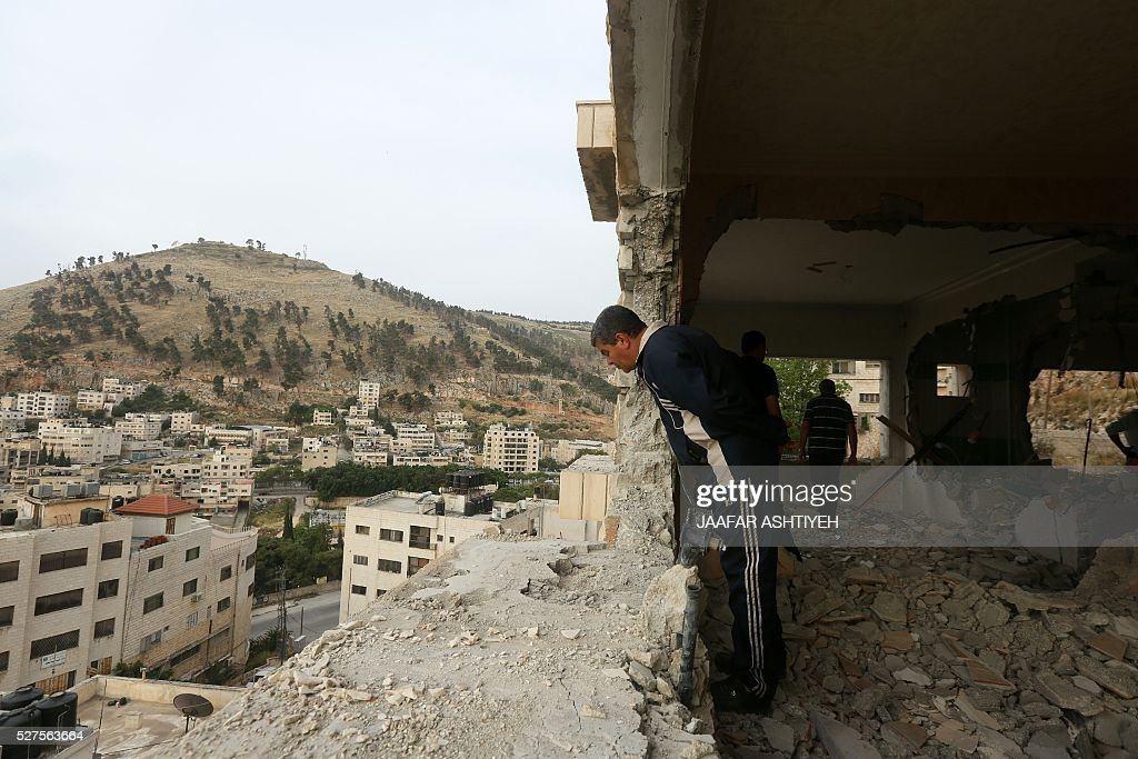 Palestinians look at the damage in the West Bank city of Nablus on May 3, 2016, after Israeli forces destroyed the house of Zaid Amer, a Palestinian man accused of taking part in the killing of a Jewish settler couple near the settlement of Itamar in October last year. The Jewish couple was shot in front of their young children as they drove on a West Bank road between the northern settlements of Itamar and Elon Moreh. ASHTIYEH