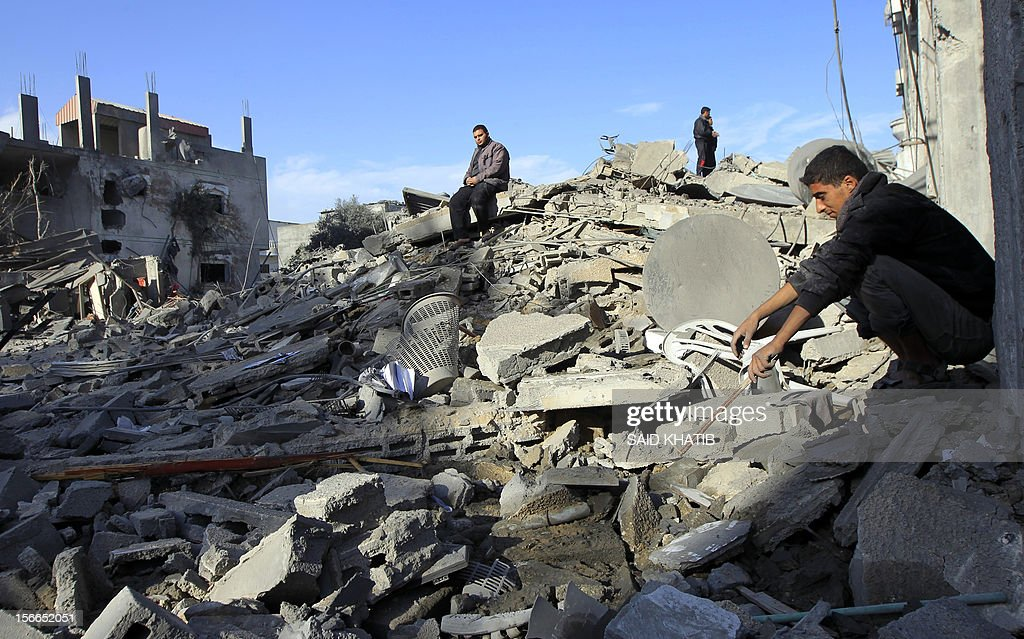 Palestinians look at their destroyed homes following Israeli air strikes on the southern Gaza Strip town of Rafah on November 18, 2012. Israeli war planes hit a Gaza City media centre and homes in northern Gaza in the early morning, as the death toll mounted, despite suggestions from Egypt's President Mohamed Morsi that there could be a 'ceasefire soon.' AFP PHOTO/ SAID KHATIB