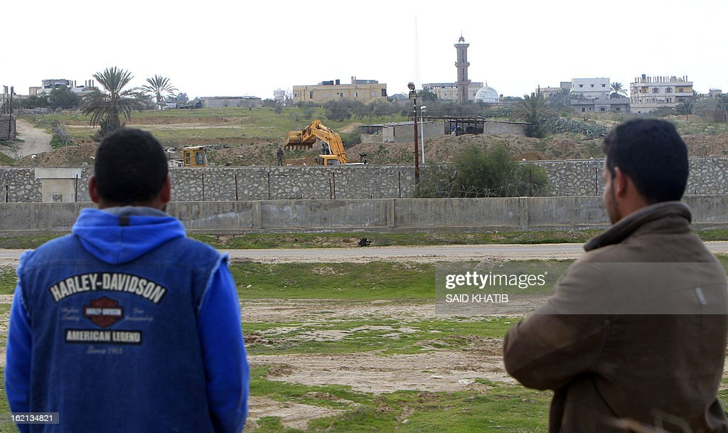 Palestinians look on as an Egyptian army bulldozer destroys smuggling tunnels along the border with Gaza, in the southern Gaza Strip on February 19, 2013. Gaza's Hamas rulers have closed hundreds of tunnels running under the territory's border with Egypt due to health concerns over some smuggled items, an official said. The tunnels have been a vital lifeline for the flow of goods and fuel into the impoverished territory, which Israel has blockaded since 2006. AFP PHOTO / SAID KHATIB