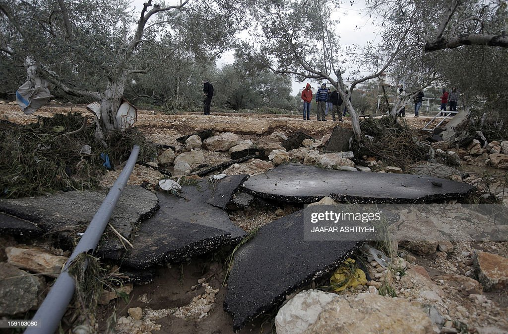 Palestinians look on in area where two girls drowned as civil defence workers and volunteers search for their bodies following flooding in the West Bank city of Tulkarem on January 9, 2013. Two women were declared dead after flooding in the northern West Bank swept their car away, as a fierce storm whipped the region, and forecasters predicted snow as temperatures dropped.