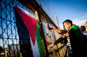 Palestinians look through a fence adorned with flags and posters next to Betunia checkpoint as they prepare for the release of Palestinian prisoners...