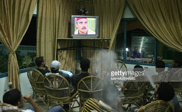 Palestinians men blow smoke from their waterpipes as they watch the Syrian drama series 'Bab alHara ' in a cafe in Gaza City 08 October 2007 The...