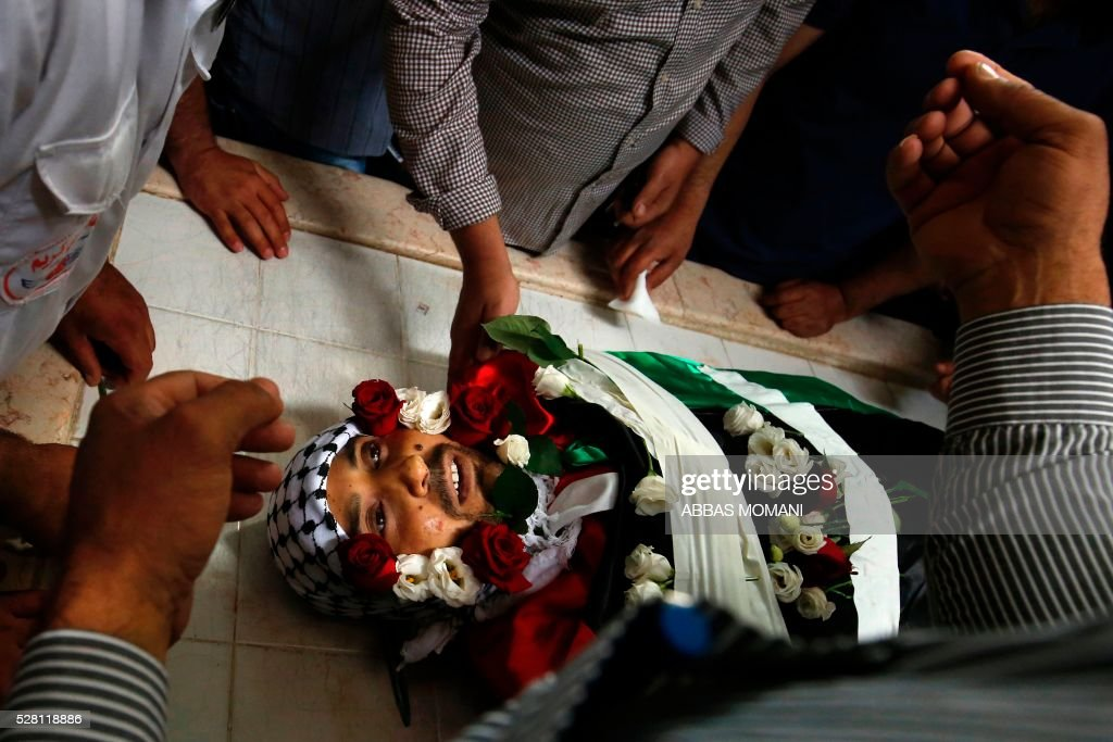 Palestinians mourn over the body of Ahmed Shahaada, 36, who was shot dead by Israeli troops after ramming his vehicle into three Israeli soldiers in the occupied West Bank, during his funeral in Betunia, near the city of Ramallah, on May 4, 2016. A Palestinian rammed his car into a group of Israeli soldiers in the occupied West Bank on May 3, injuring three before being shot dead, the Israeli army said. The army later confirmed that the injured were soldiers, and said they were taken to hospital for treatment without giving further details. MOMANI