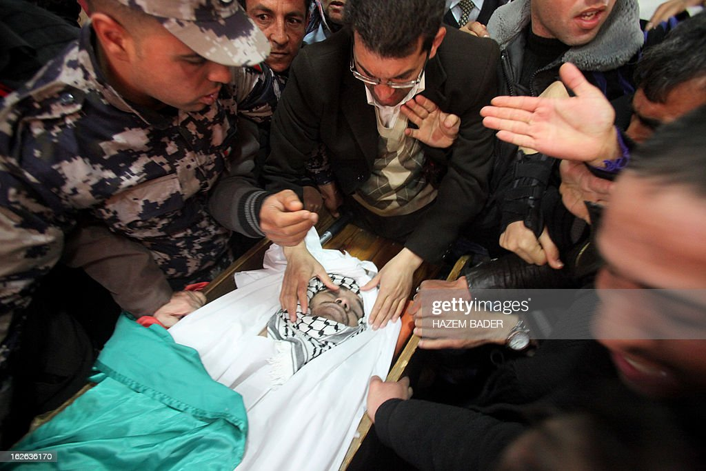 Palestinians mourn over the body of Arafat Jaradat, an inmate who died in an Israeli prison, during his funeral in the West Bank village of Saair on February 25, 2013. Militants of the Al-Aqsa Martyrs Brigades, the armed wing of Palestinian president Mahmud Abbas' Fatah movement, vowed to avenge the death of Jaradat, a prisoner they say was tortured in an Israeli jail. AFP PHOTO/HAZEM BADER