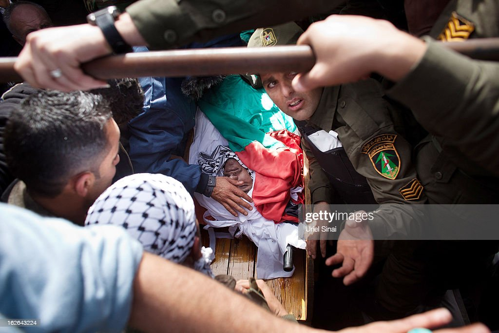 Palestinians mourn over the body of Arafat Jaradat during his funeral on February 25, 2013 in the village of Saair in the West Bank. According to reports, Jaradat died while in Israeli custody under disputed circumstances, with Palestinian officials saying an autopsy showed he was tortured.