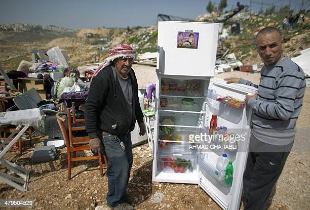 Palestinians open a fridge which they collected from their belongings after their house was demolished by Israeli bulldozers in the Arab east...
