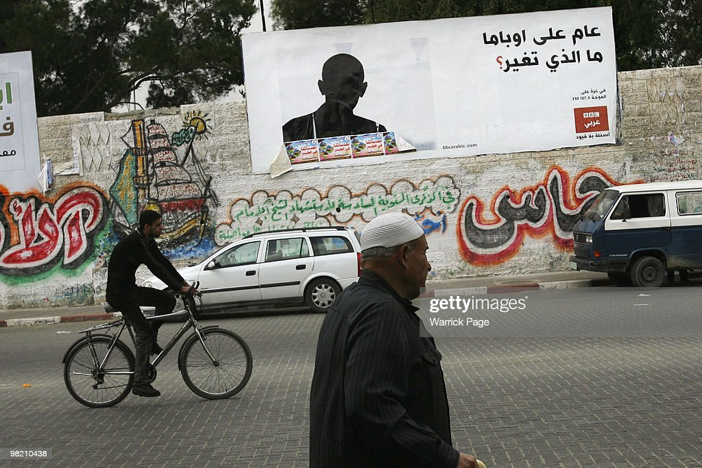 Palestinians pass an Arabic newsradio billboard featuring the shilouette of US President Barack Obama asking 'One year in office has anything...