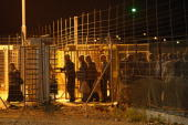 Palestinians pass between electronic fences and secure gates as they cross from the West Bank town of Qalqilya to work in the Jewish state at the...
