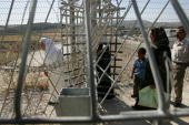 Palestinians pass through the Israeli army checkpoint June 25 2007 at Hawarra on the outskirts of the West Bank city of Nablus Israeli Prime Minister...