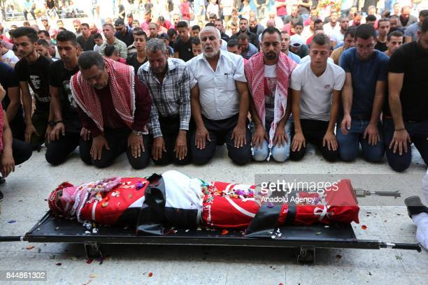 Palestinians perform a prayer during a funeral ceremony for Raid esSalihi a Palestinian prisoner who was first shot and injured and died afterwards...