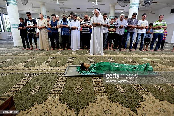 Palestinians perform funeral prayer for a Palestinian boy named Ahmad alKayd killed in Israeli shelling on Deir Al Balah during his funeral service...