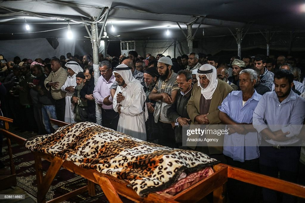 Palestinians perform prayers during a funeral ceremony held for Zine al-Umur, 55, who lost her life after Israeli warplanes bombed around Gaza's southern, in east of the Rafah city, Gaza on May 5, 2016.