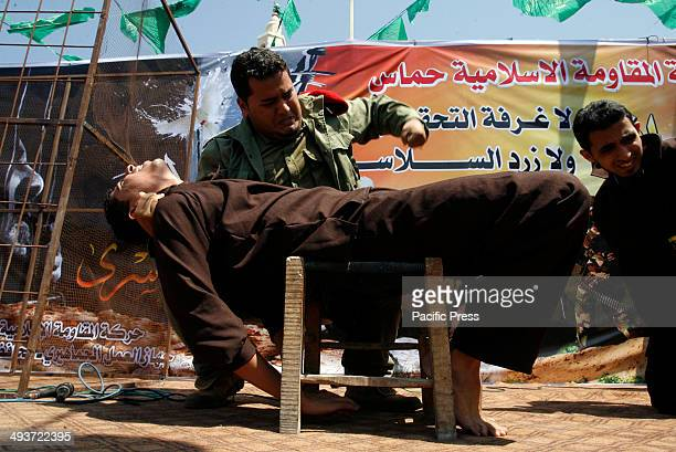 Palestinians play the role of prisoners and an Israeli soldier during a rally to show solidarity with Palestinian prisoners held in Israeli jails in...