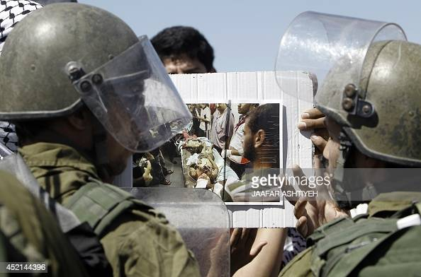 Palestinians protest at the Hawara Israeli manned checkpoint at the entrance of the northern Palestinian city of Nablus in the occupied West Bank on...