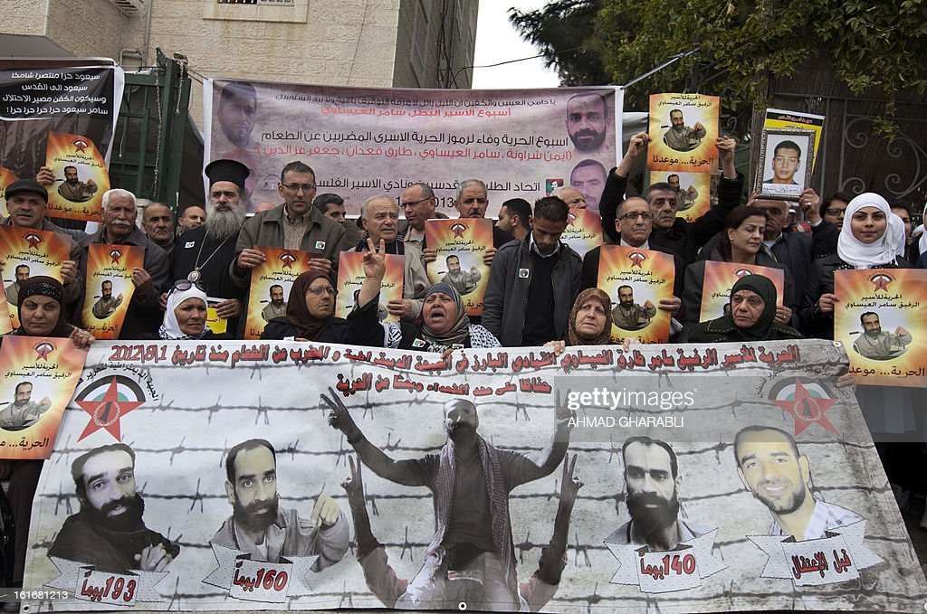 Palestinians protesters hold portraits of Samer Issawi, a Palestinian prisoner who has been on hunger strike for more than 200 days, during a solidarity sit-in outside the Red Cross offices in Jerusalem, on February 14, 2013. A United Nations official expressed concern about the well being of Palestinian detainees in Israeli prisons and in particular about the condition of hunger striker Issawi. AFP PHOTO/AHMAD GHARABLI