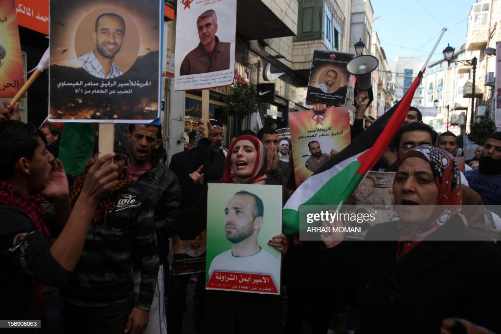 Palestinians protestors hold their national flag and pictures of relatives who are on hunger strike in Israeli prisons during a demonstration calling for their immediate release in the West Bank city of Ramallah on January 3, 2013.