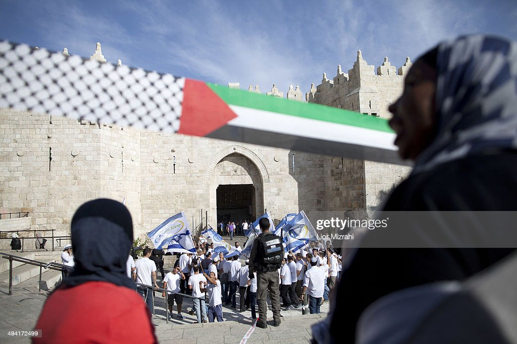 Palestinians protestors stand infront Israelis with flags marking Jerusalem Day on May 28, 2014 outside Jerusalem's old city, Israel. Israel is celebrating the anniversary of the 'unification' of Jerusalem, marking 47 years since it captured mainly Arab east Jerusalem during the 1967 Middle East war.