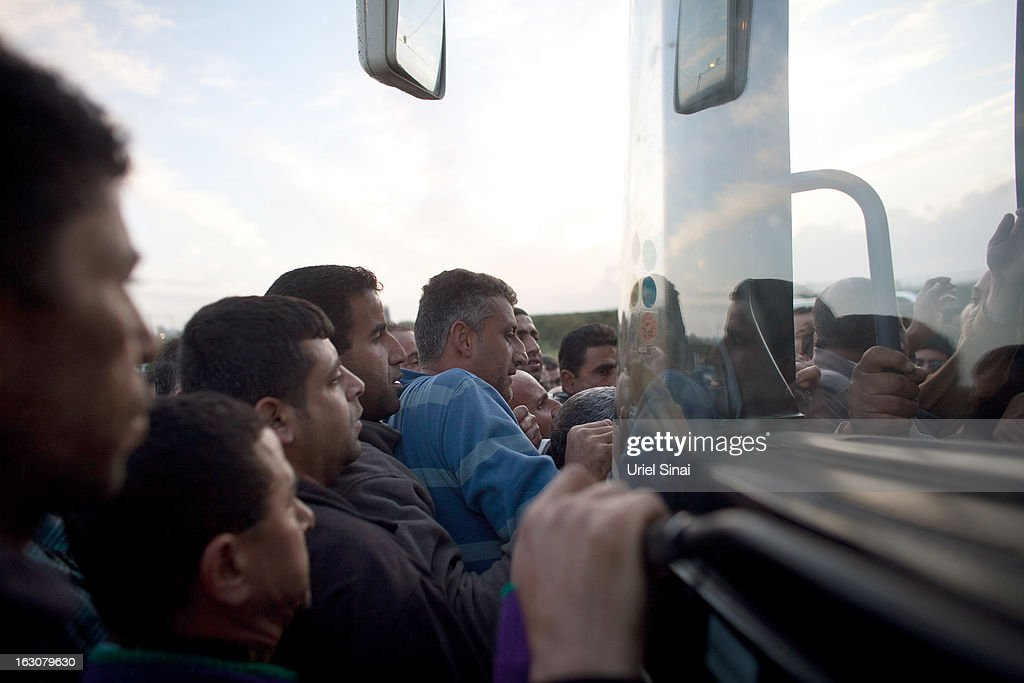 Palestinians push their way on board a bus as a new line is made available by Israel to take Palestinian labourers from the Israeli army crossing of Eyal, near the West Bank town of Qalqilya, into the Israeli cities, on March 4, 2013. at Eyal crossing, West Bank.The new line service to ferry Palestinian workers from the West Bank to Israel, encouraging them to use it instead of traveling with Israeli settlers on a similar route.
