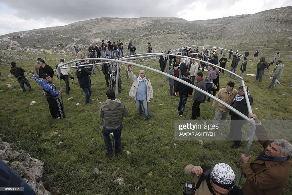 Palestinians put metal structures as they set up a new camp to protest against Jewish settlements near the West Bank village of Burin on February 2, 2013. An AFP correspondent said the Israeli army used tear gas and violence to remove hundreds of people who had set up four temporary huts and three tents near Burin, south of Nablus in the occupied West Bank, in a third attempt at the novel form of protest against Jewish settlements.