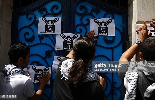 TOPSHOT Palestinians put up posters reading in Arabic 'Closed by the order of the guys ' at the entrance of the United Nations Development Programme...