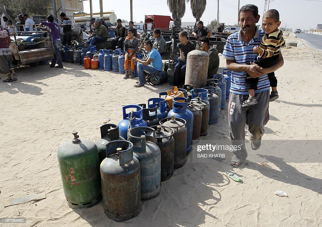 Palestinians queue to have their cooking gas bottles refilled in Rafah, in the southern Gaza Strip on November 6, 2013. Palestinian officials said Israel has limited the quantity of cooking gas entering into Gaza, which causes a shortage. AFP PHOTO/ SAID KHATIB