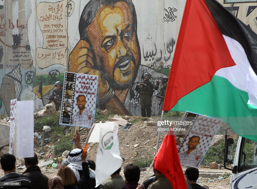 Palestinians raise up flags and placards a rally commemorating the 37th anniversary of 'Land Day', in front of the Israeli separation barrier covered with grafittis on March 30, 2013 near the Qalandia checkpoint in the Israeli occupied West Bank. Nearly 200 Palestinians clashed with Israeli forces in Qalandia, who responded with tear gas. AFP PHOTO/ ABBAS MOMANI