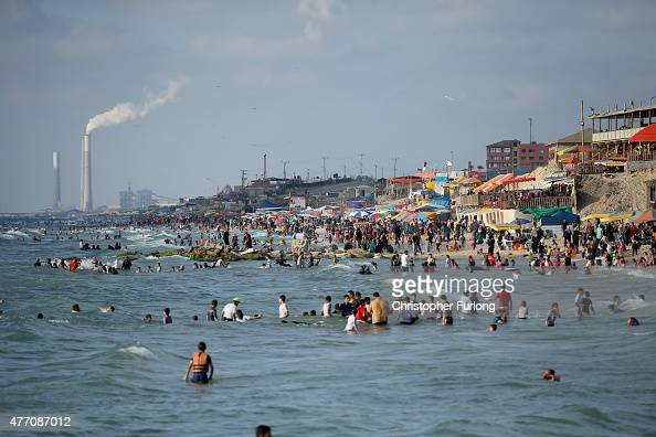 Palestinians relax and spend leisure time on Gaza Beach in the shadow of Ashkelon power station across the border in Israel on June 13 2015 in Gaza...