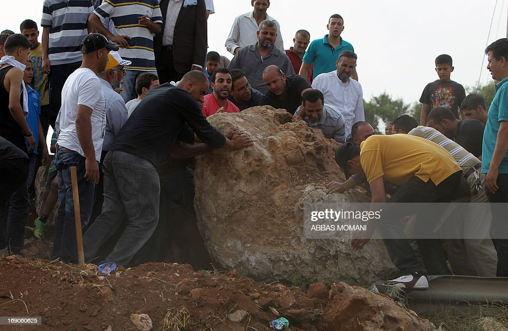 Palestinians remove a rock from a makeshift road block on the road leading to the West Bank village of Deir Jarir, east of Ramallah on May 19, 2013 after Israeli soldiers closed it the previous day due to ongoing clashes with Palestinian demonstrators. AFP PHOTO/ ABBAS MOMANI