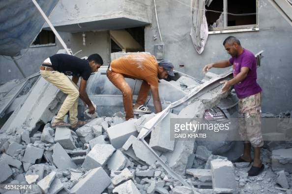 Palestinians remove debris from the wreckage of a car after a nearby house was hit by an Israeli military strike in Rafah in the southern Gaza Strip...