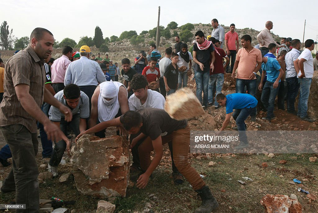 Palestinians remove rocks from a makeshift road block on the road leading to the West Bank village of Deir Jarir, east of Ramallah on May 19, 2013 after Israeli soldiers closed it the previous day due to ongoing clashes with Palestinian demonstrators.